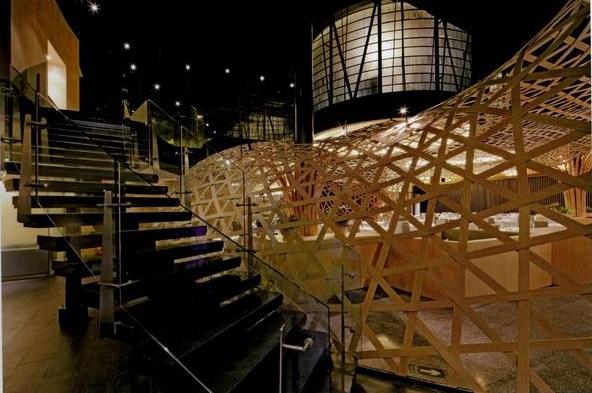 本餐厅设计案选用复合的竹板为主材料,强调传统与现代相结合的餐厅装修设计主题。  利用餐厅中原有的层高优势,设计师将部分竹板悬吊于顶上,创造出高低层次的趣味性,丰富了空间的视觉感受。大厅中心的核心筒和侧边悬挑的半椭圆型体块显得零碎杂乱,设计师采用一片由竹篾编织、从墙面延伸至天花板的巨大顶棚,将空间重新塑造,构筑了大厅梦幻般的场景。而视线穿过透空的竹网,顶棚保持了原有的层高优势,亦使得上下空间形成了微妙的互动关系。在原有的核心筒上,设计师以透光竹板包裹四壁形成灯箱光源,使原本沉重的混凝土体量变为空间中的焦点